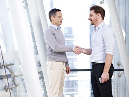 reconocimiento: dos personas de negocios caucásicos agitando las manos en edificio de oficinas moderno.