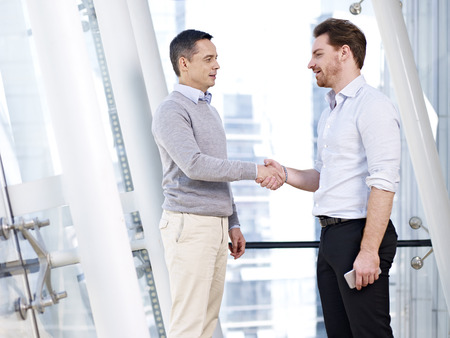 welcoming: two caucasian business persons shaking hands in modern office building. Stock Photo