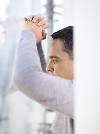 persona deprimida: deprimida persona de negocios caucásico mirando por la ventana y pensando en el moderno edificio de oficinas. Foto de archivo