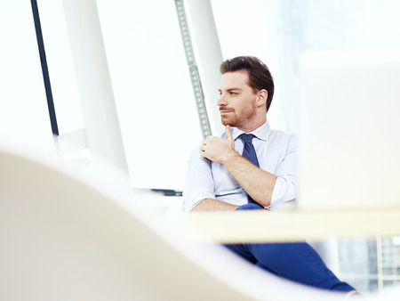 cogitate: caucasian businessman sitting at desk thinking in office.