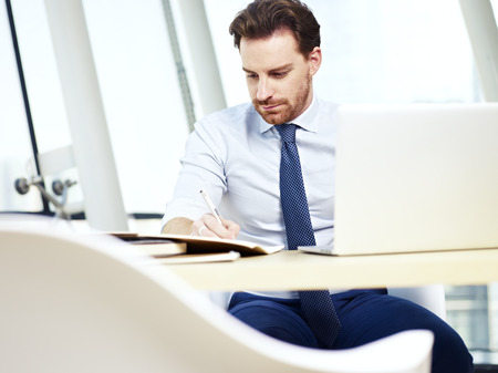 documenting: caucasian businessman sitting at desk taking notes while using laptop computer in office.