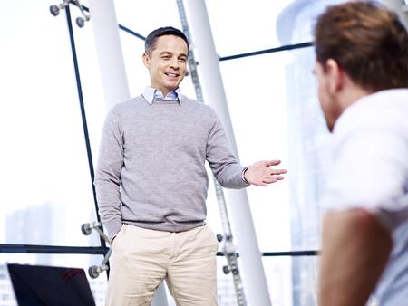 話を事務所でディスカッション話し合いを持つ白人ビジネスマン。