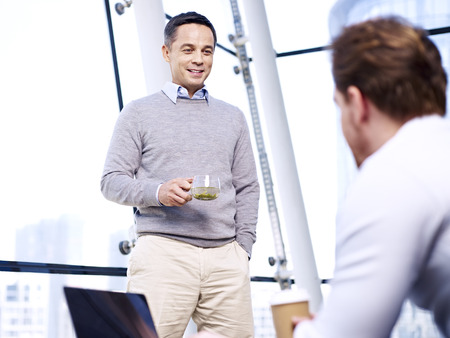 westerner: caucasian business people talking having a discussion conversation in office. Stock Photo