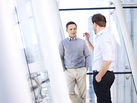 dialogo: la gente de negocios caucásico que habla de tener una conversación discusión en el cargo. Foto de archivo