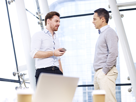 casual men: caucasian business people talking having a discussion conversation in office. Stock Photo