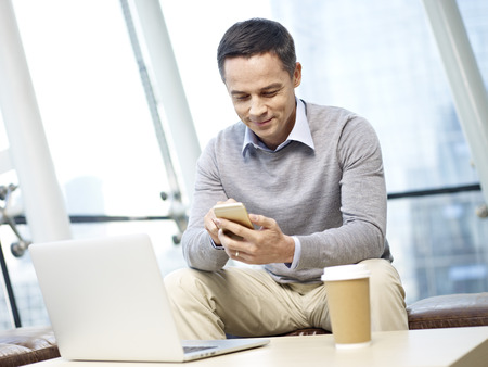 people on computers: man in business casual wear playing with mobile phone in office.