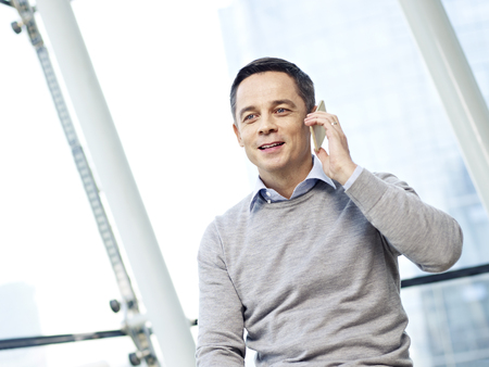 business casual: man in business casual wear making a phone call in office.