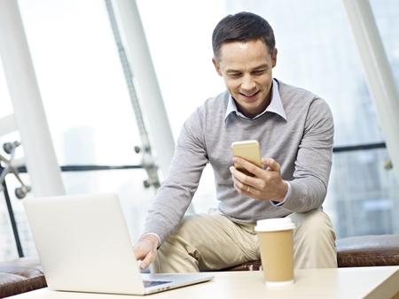 Abbigliamento Ufficio Uomo : Caucasico uomo seduto alla scrivania guardando al telefono mobile