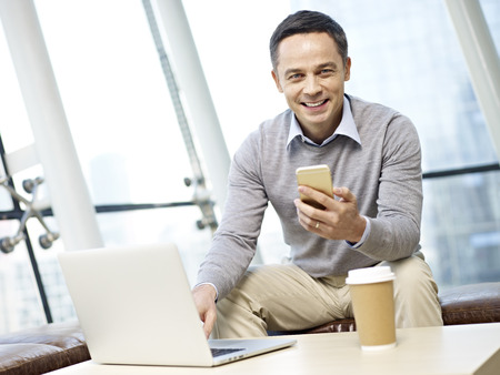man in business casual wear looking at camera smiling while using mobile phone and laptop computer in office.