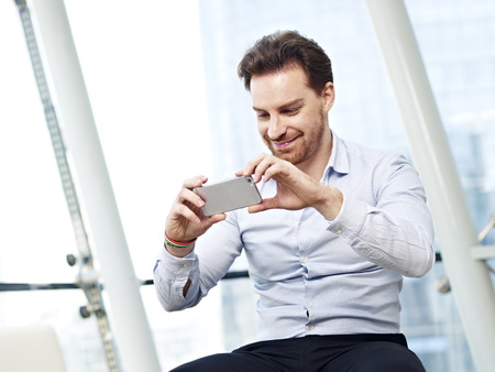 young caucasian business man looking at a picture or watching a video or taking a picture with mobile phone and smiling.