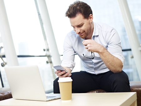 westerner: young caucasian corporate person looking at messages on cellphone and smiling. Stock Photo