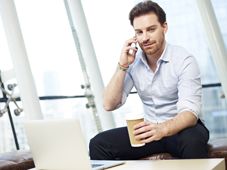 westerner: young caucasian business people making a call using mobile phone in modern office.