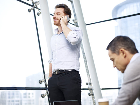 westerner: young caucasian businessman talking on mobile phone in modern office.
