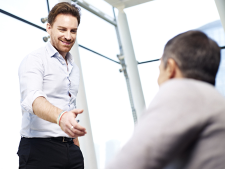 reaching out: young caucasian business executive reaching out for a handshake. Stock Photo