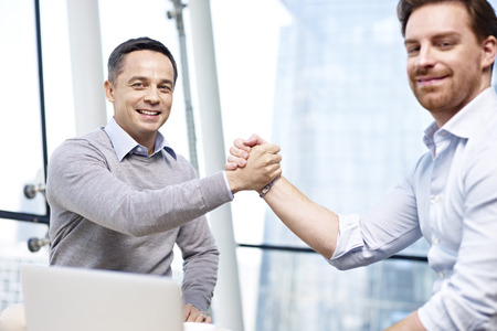 dos hombres de negocios caucásico celebrando el éxito en conjunto en la oficina.