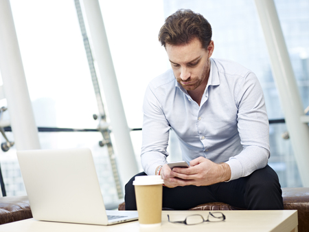 westerner: caucasian business person looking down at cellphone in office.
