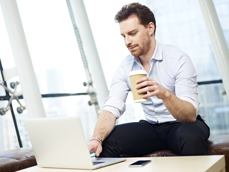 westerner: young business executive working on laptop computer hold a cup of coffee in modern office.