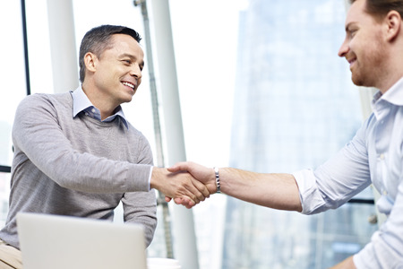 first job: two caucasian businesspeople smiling and shaking hands in office. Stock Photo