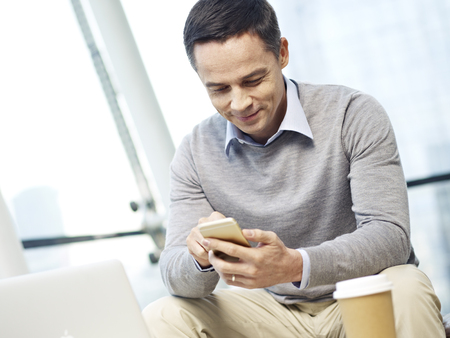 office wear: caucasian business person in casual wear checking messages on cellphone in office.