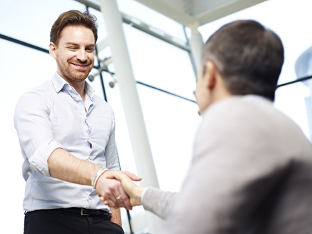 thanking: two caucasian businesspersons greeting each other by shaking hands in modern office. Stock Photo