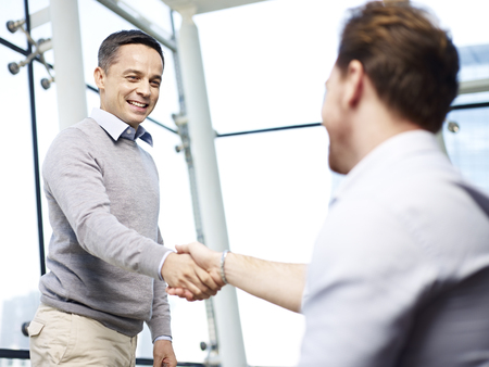 two caucasian businessmen greeting each other by shaking hands in modern office.