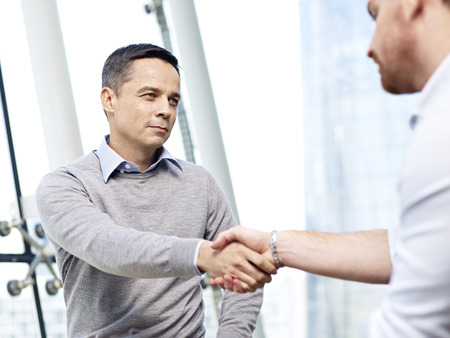 enmity: caucasian business manager in casual wear shaking hands with competitor with serious facial expression.