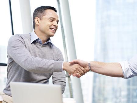 ejecutivo en oficina: ejecutivo de negocios caucásico sonriendo y agitando la mano con otra persona en el cargo. Foto de archivo