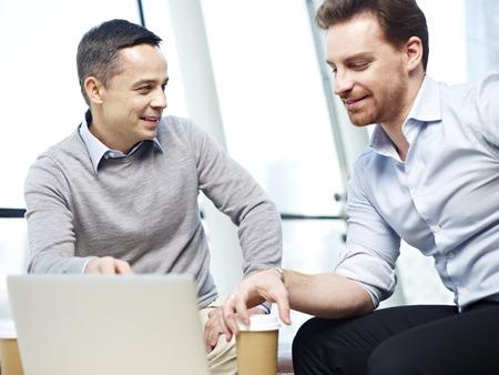 armonia: dos trabajadores de oficina caucásicos en ropa de sport se habla de negocios en la oficina.