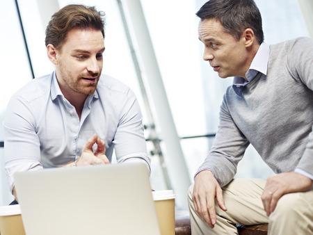 dialogo: dos ejecutivos de empresas caucásicos en ropa de sport que tienen una discusión en la oficina de negocios.