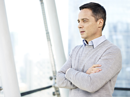 deliberation: caucasian businessman in casual wear standing and thinking by the windows in office. Stock Photo