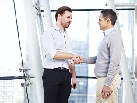 ejecutiva en oficina: dos ejecutivos de negocios caucásicos en ropa de sport dar la mano en la oficina. Foto de archivo