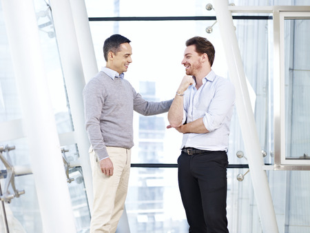 first day: caucasian business executive praising subordinate by giving a pat on the shoulder.