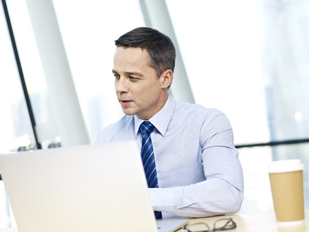 person computer: caucasian corporate person in shirt and tie looking away and thinking while working on laptop computer in office.