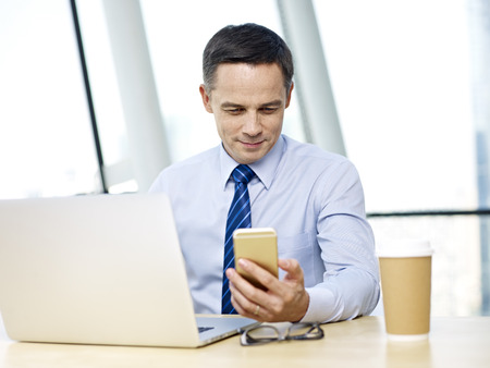 caucasian business person in shirt and tie checking cellphone while working on laptop computer in office.