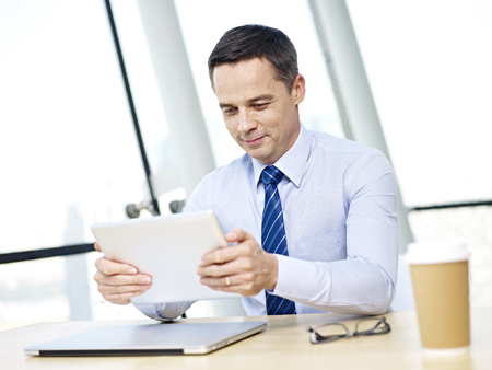 westerner: caucasian business executive sitting at desk using tablet computer in office.