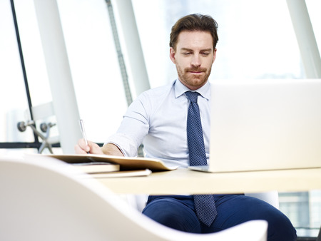 westerner: caucasian business man looking at laptop screen thinking in office. Stock Photo