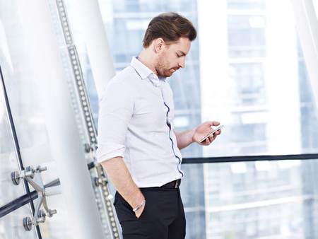 tweeting: caucasian business person standing by the window looking at mobile phone in modern office building. Stock Photo