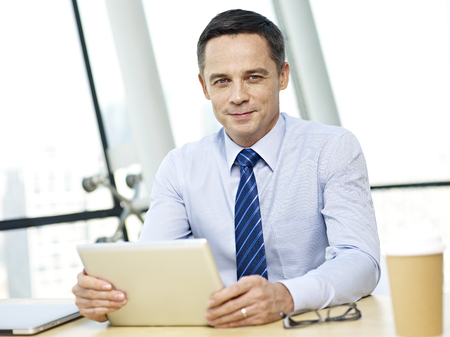 westerner: caucasian business executive sitting at desk looking at camera holding tablet computer in office.