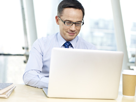 writing western: caucasian businessman sitting at desk looking at laptop computer and smiling in office.