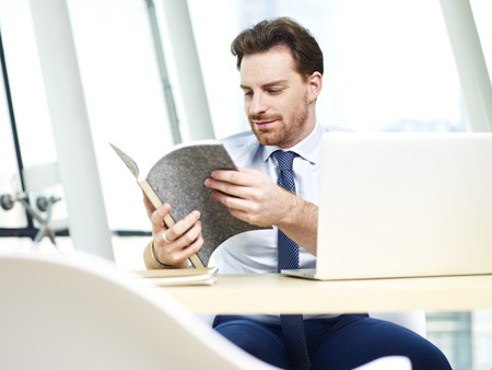 westerner: caucasian business man looking through notes while working on laptop computer in office. Stock Photo