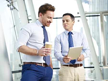 westerner: two caucasian corporate people discussing business using tablet computer in office. Stock Photo