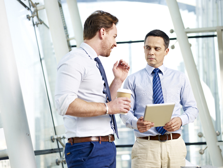 business skeptical: two caucasian businessperson having a serious discussion on business in office.