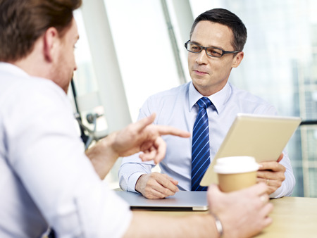 appraising: caucasian corporate people having a discussion in office.