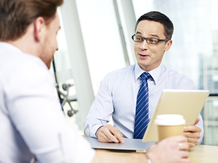 responding: caucasian business man responding to coworker during a conversation in office. Stock Photo