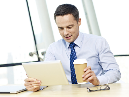 westerner: caucasian businessman looking at tablet computer holding coffee cup smiling in office.