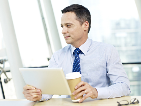 westerner: caucasian businessman holding tablet computer and coffee cup looking away thinking in office.