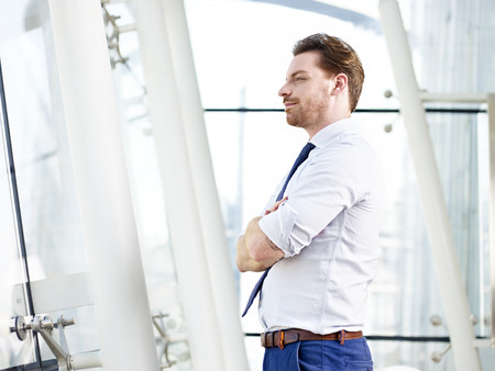 westerner: caucasian corporate person standing in office looking out of window thinking, arms crossed.