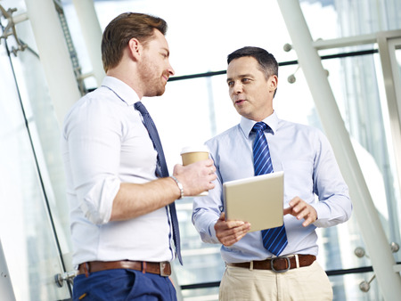 westerner: two caucasian business executives talking about business in office.