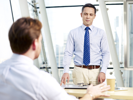 business skeptical: caucasian business manager listening to colleagues explanation during a meeting in office. Stock Photo