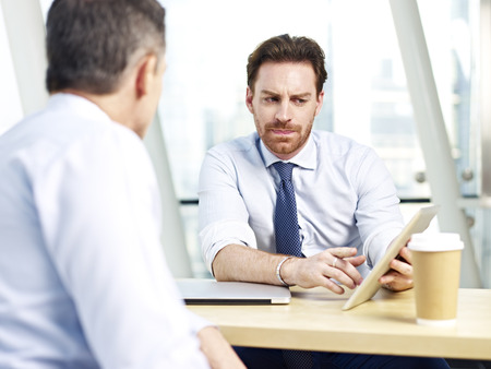 westerner: two caucasian office people discussing business using tablet computer in office. Stock Photo